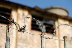 Rusty barbed wire on a fence of a deserted industrial ruin royalty free stock photo