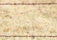 Rusty Barbed Wire Frame. A section of rusty barbed fence, framing a blurred light brown background. Can be used as frame, border or background stock images