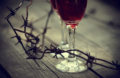 Rusty barbed wire and glasses with red wine. Stock Photo