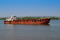 A rusty barge on a river. Indian cargo on rusty barge against a blue sky Royalty Free Stock Photography