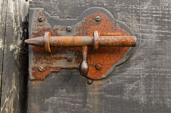 Rusty barn latch. Old rusty barn latch in a wooden door Royalty Free Stock Images