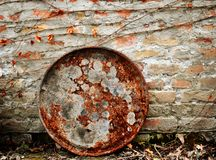 Rusty barrel lid on red brick wall and dry ivy branch and leaves royalty free stock image