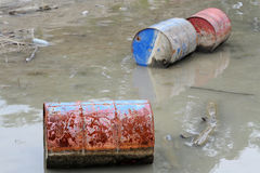 Rusty barrels floating in river Royalty Free Stock Photos