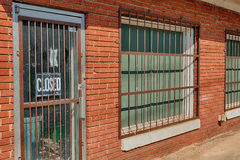 Rusty Bars On Old Deserted Building. An abandoned business sits vacant in a high-crime area Royalty Free Stock Images