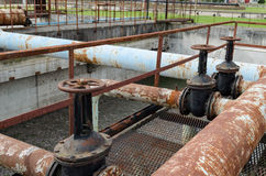 Rusty big tap and pipes and water treatment liquid Royalty Free Stock Photos