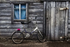 Rusty bike. The bike against the wall of an old house Stock Photos