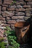 Rusty Bin vid stenväggen royaltyfri fotografi