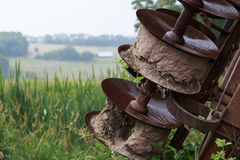 Rusty blades of farm equipment in a grassy field on a sunny day Stock Photography