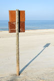 Rusty board sign on wooden post on a beach Royalty Free Stock Images
