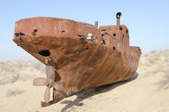 Rusty boat on the Aral Sea. Rusty boat stranded on the now dry bottom of the Aral Sea. The sea has dried up, leaving only sand, seashells, rusty boats and unique Royalty Free Stock Photography