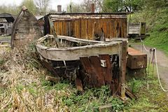Rusty boat on the green grass. Rusty decay fish boat on the green grass Royalty Free Stock Photo