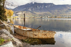 Rusty boat. An old rusty boat chained on the lake shore stock photo