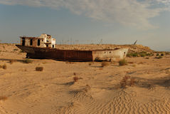Rusty boat shell lying in the desert. Rusty ship lying in the sand at the former Soviet Aral Sea port of Moynaq in Uzbekistan Stock Image
