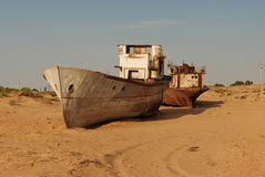 Rusty boat shell lying in the sand. Rusty ship lying in the sand at the former Soviet Aral Sea port of Moynaq in Uzbekistan Royalty Free Stock Images