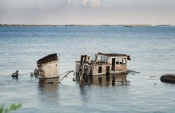 Rusty boat wreck in a blue river royalty free stock image