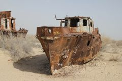 Rusty boats of the Aral Sea. Boats stranded on the now dry bottom of the Aral Sea. The sea has dried up, leaving only sand, seashells, rusty boats and unique and Royalty Free Stock Image