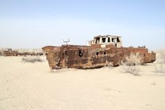 Rusty boats of the Aral Sea. Boats stranded on the now dry bottom of the Aral Sea. The sea has dried up, leaving only sand, seashells, rusty boats and unique and Stock Photos