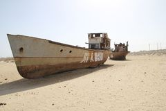 Rusty boats of the Aral Sea. Boats stranded on the now dry bottom of the Aral Sea. The sea has dried up, leaving only sand, seashells, rusty boats and unique and Royalty Free Stock Photography