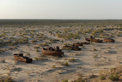 Rusty boats of former Aral  fishing fleet. Rusty ship lying in the sand at the former Soviet Aral Sea port of Moynaq in Uzbekistan Royalty Free Stock Photography