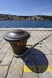 Rusty bollard in Mali Losinj, Croatia. Vertical composition of a traditional rusty bollard on the seafront of Mali Losinj, Croatia, a popular travel destination Stock Photo