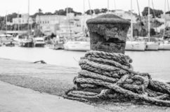 Rusty bollard with rope in bw stock photo