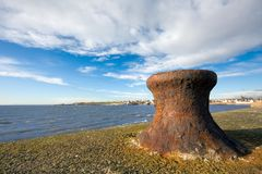 Rusty bollard on a sea wall. A rusty bollard on a sea wall in early morning light with blue skies. Photo taken in Anstruther, Scotland Royalty Free Stock Image