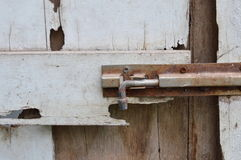 Rusty bolt on decay white wooden door Stock Photography