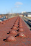 Rusty bolts on bridge. A closeup view of rusty and peeling paint on old bridge bolts Royalty Free Stock Photo