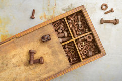 Rusty bolts. In the wooden box Stock Photos