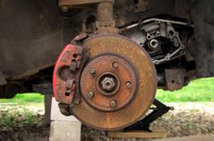 Rusty brake disc on a broken car in the yard stock image