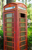 Rusty British telephone booth. This vintage telephone booth has been upcycled as yard art in a flower garden Stock Photography