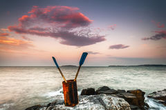 Rusty bucket with oars. Rusty bucket with two oars by the sea shore at sunset Stock Photo