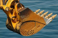 Rusty bulldozer scoop over water Royalty Free Stock Photography