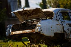 A rusty, burnt-out car with no taillights on the road in the mountains. stock photos