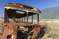 Rusty bus wreck in arid landscape Royalty Free Stock Image