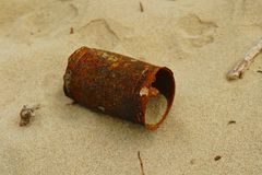 Rusty can on beach. An old and rusty tin can in a state of complete decay on a beach, filled with sand, wide view Royalty Free Stock Photo