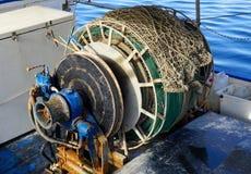 Rusty capstan winch of trawler fishing boat with fishing net on it stock photo