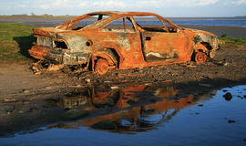 Rusty car. Rusty burned out car sitting on foreshore stock photography