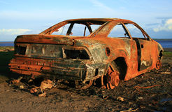 Rusty car. Rusty burned out car sitting on foreshore royalty free stock photography
