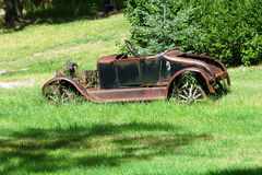 Rusty Car. An old rusty car, overgrown with vegetation, rests in a grassy field in Montana Stock Images