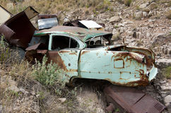 Rusty car in desert. Old abandoned hillside  town dump in American desert with autos, washers, oil heaters and refrigerators Stock Images
