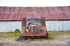 Rusty Car framme av rostig byggnad Arkivfoto