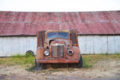 Rusty Car in front of rusty building. Stock Photo