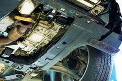 Rusty Car Undercarriage. Closeup Photo. Car in Auto Service. Lifted Broken Car Stock Photo