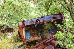 Rusty car wreck abandoned in a wood Royalty Free Stock Photo