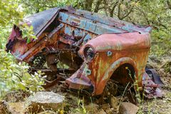 Rusty car wreck abandoned in a wood Stock Photos