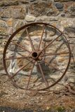 Rusty cart wheel resting against a stone wall no. 2 royalty free stock photo