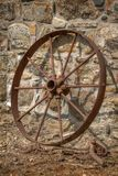 Rusty cart wheel resting against a stone wall stock image