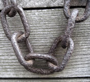 Rusty Chain. A rusty old chain, hanging over wooden planks royalty free stock photos