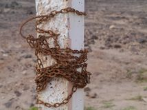 A rusty chain around a concrete pole Royalty Free Stock Photo